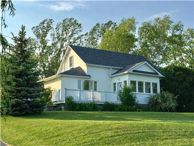 Charming farmhouse on a beautiful acre overlooking the sparkling waters of Prince Edward Bay in PEC