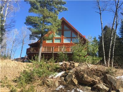 A large log home, waterfront on River Joseph, Aumond, QC, 1 - 1/2 story, and walkout basement