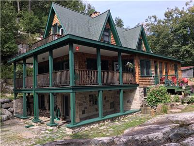 6 acres of privacy. A designer cottage with beach on expansive, pristine Redstone Lake